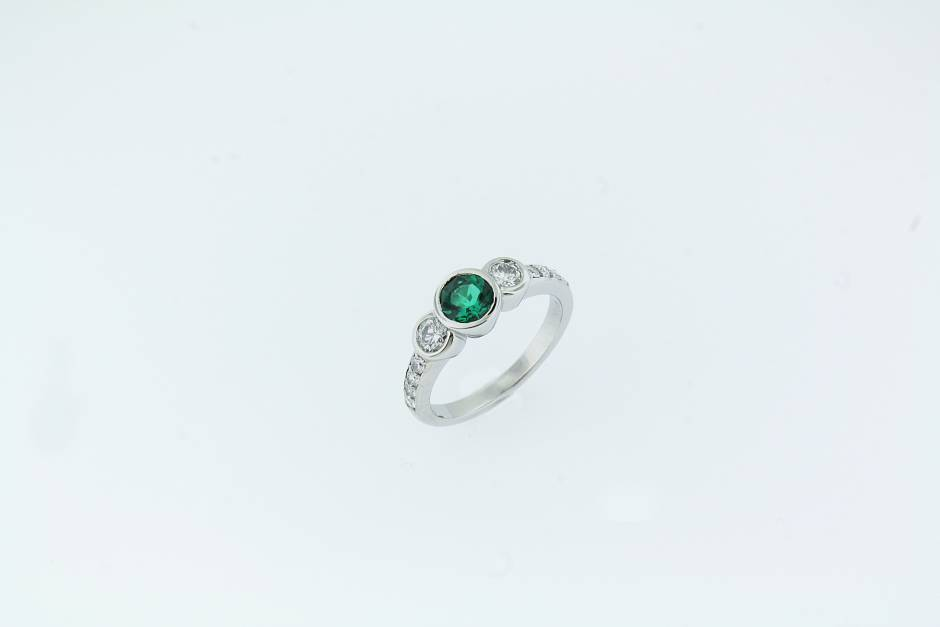 19k white gold engagement ring. - 19k white gold engagement ring with a lab grown emerald. It is flanked by two 0.15 carat round diamonds with small diamonds bead set down the shank.
