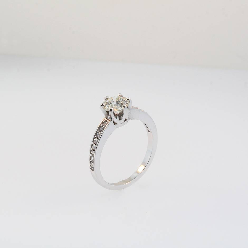 Engagement ring. - 14k white gold engagement ring. Holds a 1 carat round brilliant flanked by 8 small diamonds on each each side.