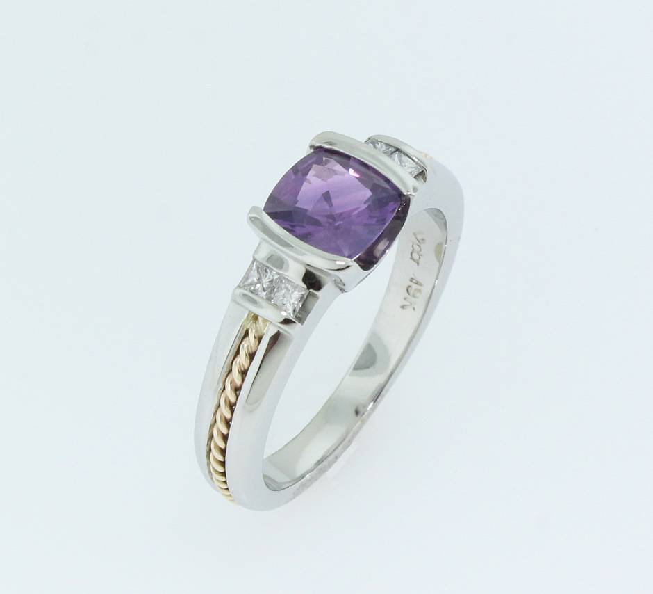 19k white gold engagement ring. - A purple sapphire in a half bezel set in a 19k white gold with a braided yellow gold inlay.