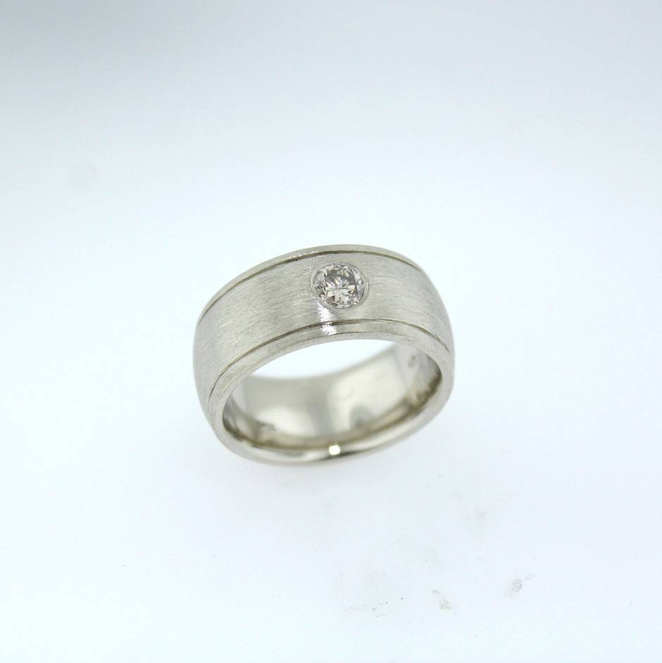 10k white gold  - wedding band surface set with a solitary diamond.