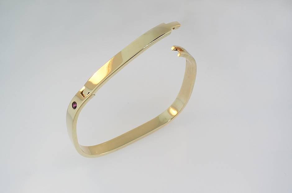 14 yellow gold hinged cuff bangle - with a surface set ruby.