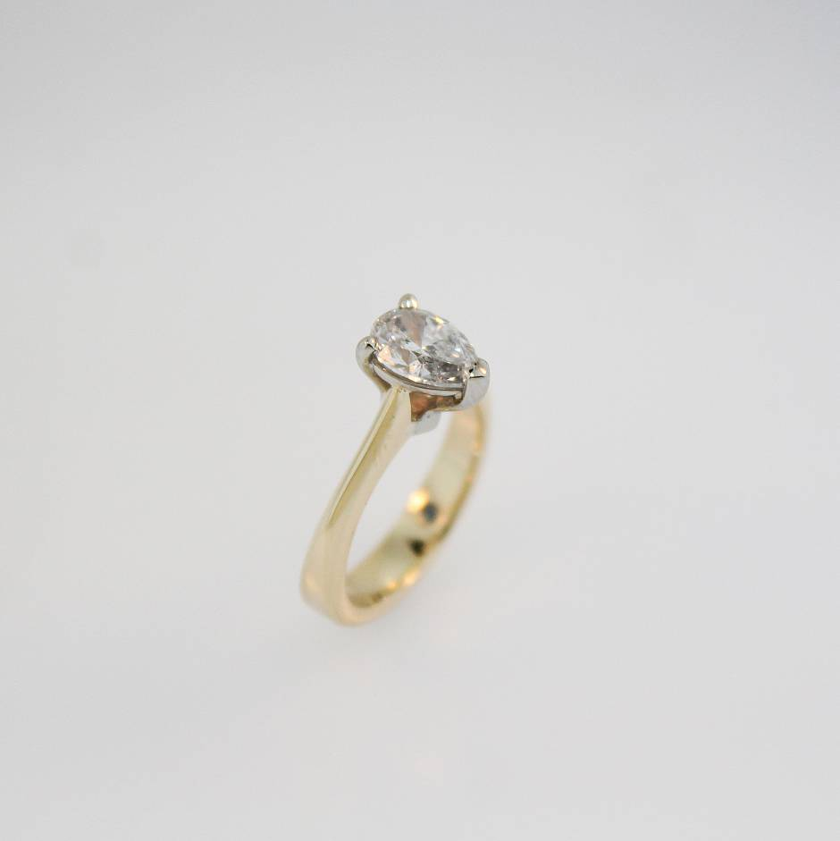 Custom engagement ring -  - holding solitaire pair shaped diamond in a 14k white gold setting and 14k yellow gold shank.