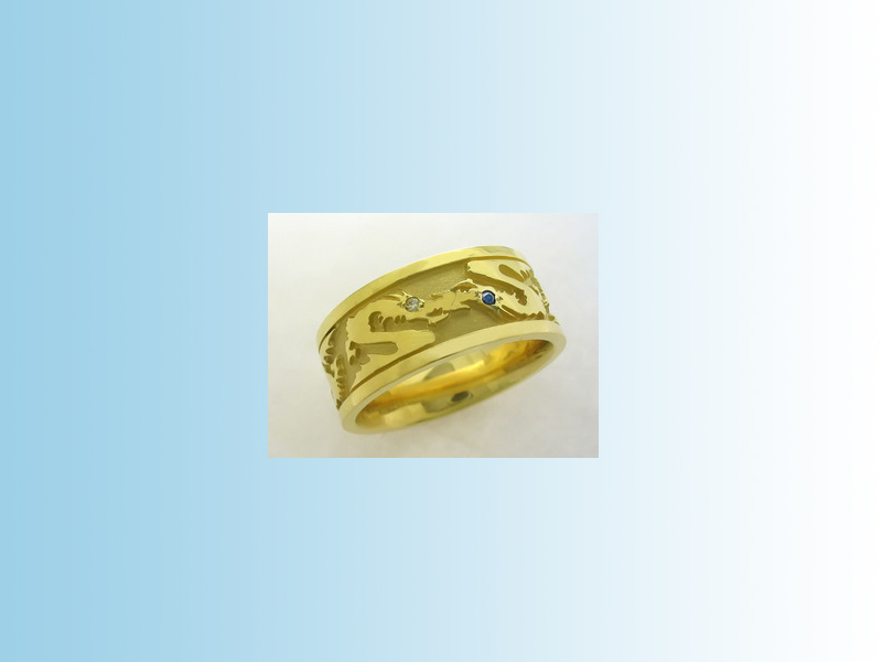 Dragon ring GWB009 - Four dragons concentrically arranged around a flat wedding band with side bands. Gems of choice are set in the eyes of the dragons. 14K yellow gold.