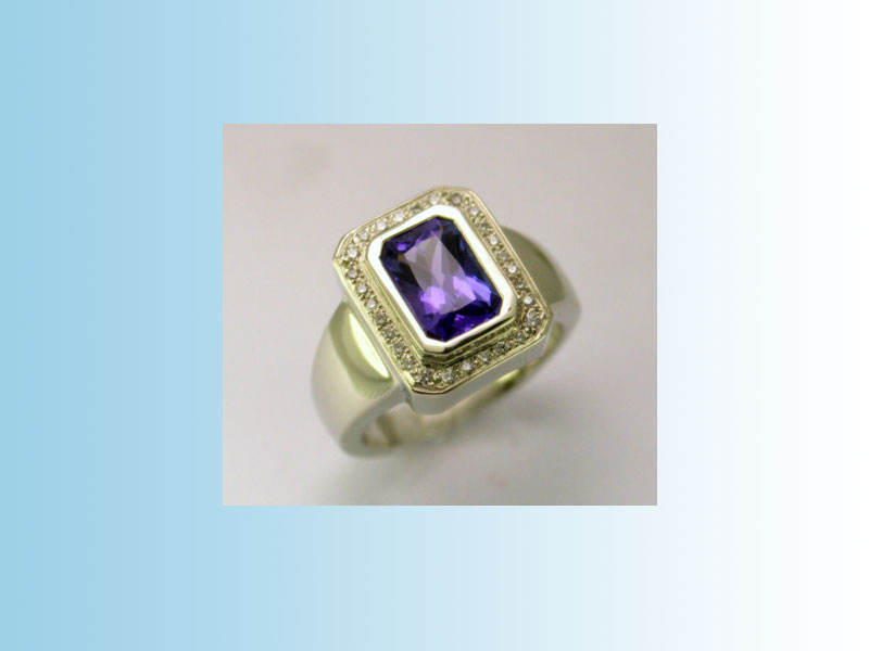 Emerald cut Tanzanite CRR003 - The tanzanite is set in a bezel with diamonds set pavé style around it. 14K white gold