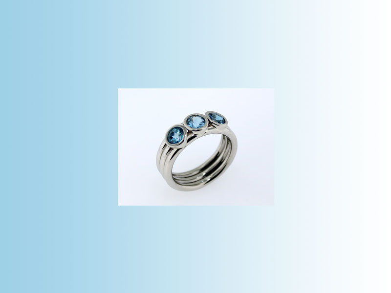 Blue topaz family ring CJP003 - 14K white gold ring consisting of three round bands and three full bezels in which three blue topaz stones are set, each of a different shade. Designed by Suzanne Spisani of Spisani Designs, Revelstoke, B.C.